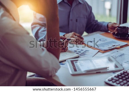 Middle-age Asian two business managers crew working with new startup project while sitting in coffee shop modern office. #1456555667