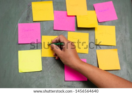 Close up woman hand writing colorful note sticky for brainstorm and share idea strategy workshop business.Brainstorming concept. #1456564640