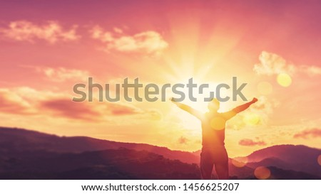 Copy space of man hand raising on top of mountain and sunset sky abstract background. Freedom travel adventure and business victory concept. Vintage tone filter effect color style. Royalty-Free Stock Photo #1456625207