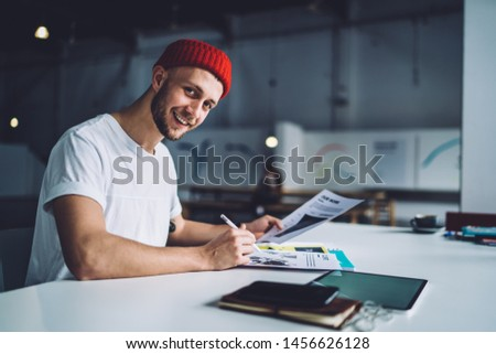 Side view of handsome smiling male in red cap sitting at desk with electronic devices working with documents and looking at camera #1456626128