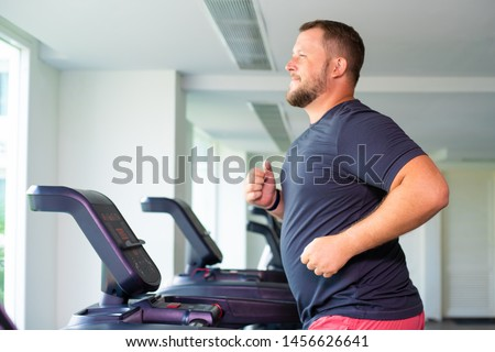 full male runs on a treadmill in a gym. concept of weight loss and sport. side view #1456626641