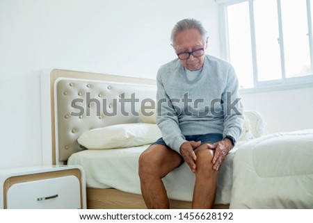 Picture of elderly man suffering from knee pain while sitting on the bedroom. Shot at home