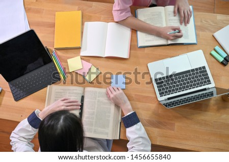 Education concept. Top view young woman reading a books. with computer and sticky note on wood table. #1456655840