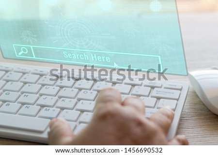 Dry hands of adult student using white keyboard and virtual screen on wood table to searching knowledge on the internet for learning. Education futuristic technology and Lifelong learning concept. #1456690532