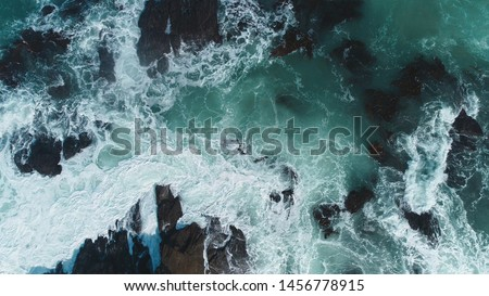 Aerial view of crashing waves on rocks. Aerial view of sea waves and fantastic Rocky coast,Background texture of a rocky shore and blue and turquoise water and waves of the Atlantic Ocean New Zealand. Royalty-Free Stock Photo #1456778915
