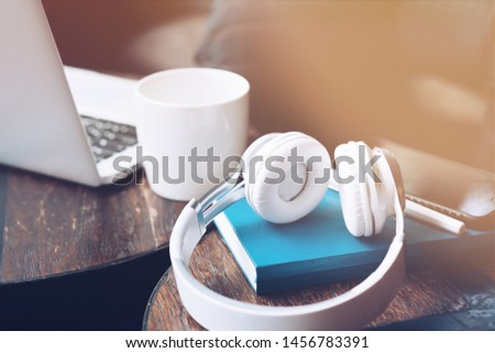 Freelancer workplace. Modern workplace with a laptop, cup of coffee, notebook and headphones on a wooden office desk background. Business and Freelance concept. Horizontal shot #1456783391