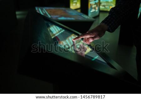 Man using interactive touchscreen display of electronic multimedia kiosk at modern museum or exhibition - scrolling and touching - close up view. Education, entertainment, learning, technology concept #1456789817