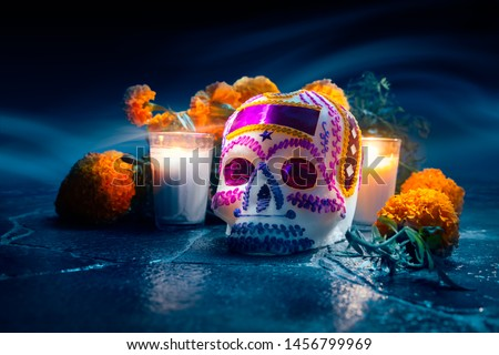 "Traditional sugar skull used at mexican offerings or ""ofrendas"" for Day of the Dead celebration with marigold or ""cempasuchil"" flowers. high contrast image Royalty-Free Stock Photo #1456799969"