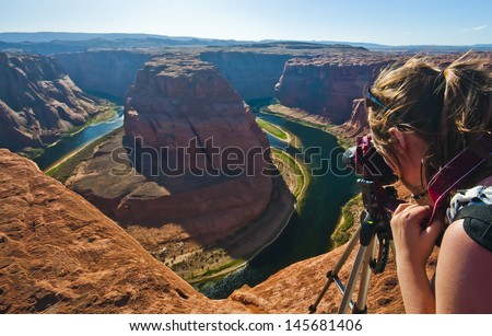 Young woman taking photograph of panoramic view of Horseshoe Bend at Utah, USA