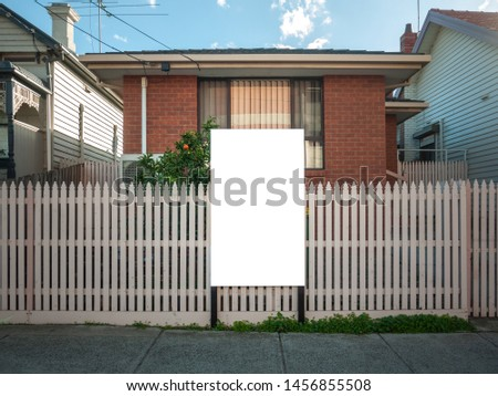 Blank white mock up template of a real estate advertisement billboard/sign/board at front of a typical residential brick house in an Australian suburb.