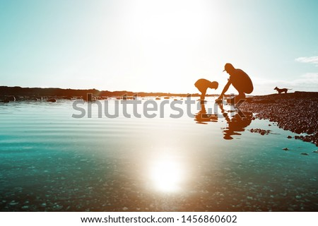 Silhouette of father and son playing on the beach at the sunset time - People having fun on summer vacation with their dog - Love, fatherhood and family #1456860602