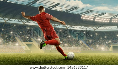 Soccer player kicks of the ball. Action. Floodlit stadium with tribunes. Royalty-Free Stock Photo #1456883117