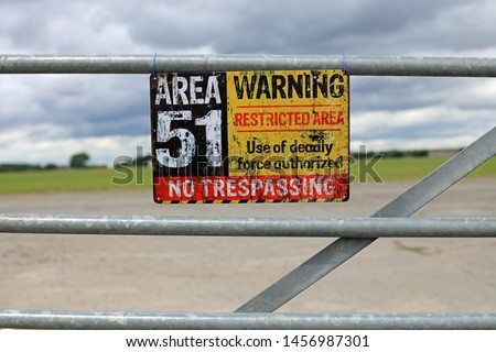 Vintage Area 51 Warning Sign Hanging On A Gate. Extraterrestrial Storage Facility Concept. Royalty-Free Stock Photo #1456987301