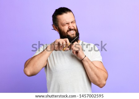 angry crazy funny man hates his beard. isolated blue background. studio shot, frustration #1457002595