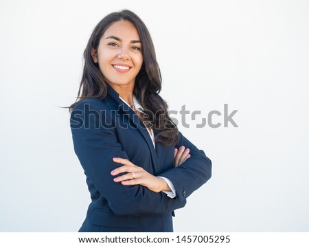 Smiling confident businesswoman posing with arms folded. Happy beautiful black haired young Latin woman in formal suit standing for camera over white studio background. Corporate portrait concept Royalty-Free Stock Photo #1457005295