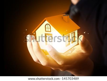 Businessman holding home model #145703489