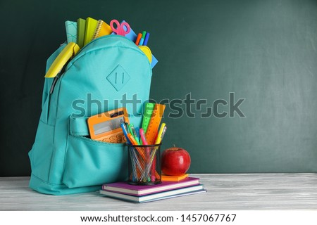 Stylish backpack with different school stationary on white wooden table at green chalkboard. Space for text #1457067767