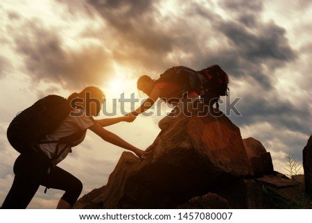 Hiking team helping each other while climbing up in a sunset. The concept of aid. Royalty-Free Stock Photo #1457080007
