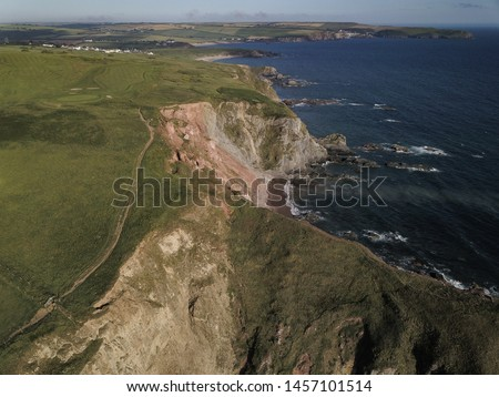 Bigbury on Sea, Devon, near Cornwall, England. Jurassic coast seaside landscape. Aerial drone view flying over ocean and beach Royalty-Free Stock Photo #1457101514