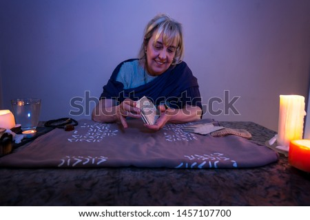 Tarot cards. Woman sits near a fortune teller desk with Tarot cards and candles. Divination and clairvoyance. #1457107700