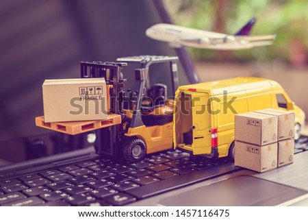 Logistics, supply chain and delivery service concept : Fork-lift truck moves a pallet with box carton. Van on a laptop computer, depicts wide spread of products around globe in ecommerce popular era #1457116475