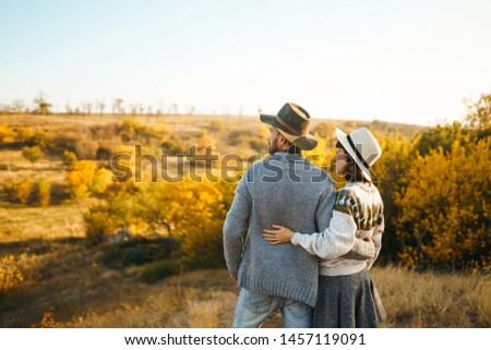 Back view. Lovely hipster couple enjoying each other. Couple wearing beautiful hats and sweaters. Lifestyle, happy couple of two play on a sunny day in the park.  #1457119091
