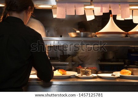 Professional restaurant kitchen with food being prepared and set on kitchen pass for waiting staff. Royalty-Free Stock Photo #1457125781