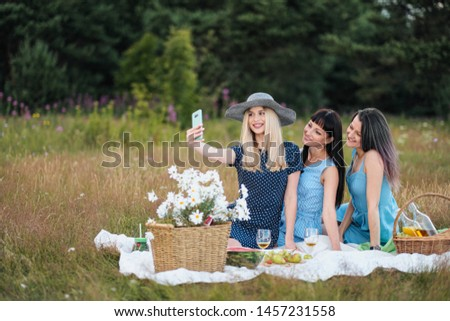 Three young women, in blue dresses and hats sit on plaid and take pictures on smartphone. Outdoor picnic on grass. Delicious food in picnic basket and wine. Watermelon, grapes and bouquet of daisies.