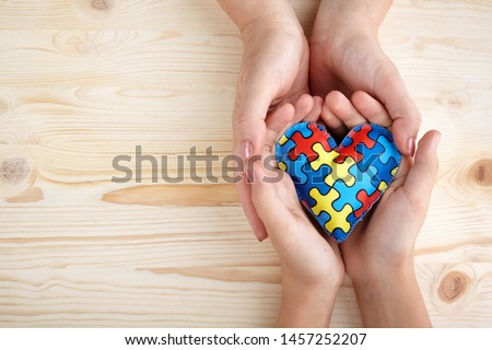 World Autism Awareness day, puzzle or jigsaw pattern on heart with autistic child's and women hands #1457252207