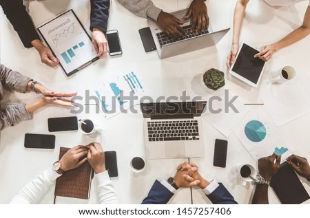 A team of young office workers, businessmen with laptop working at the table, communicating together in an office. Corporate businessteam and manager in a meeting. coworking. #1457257406