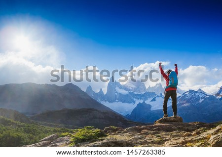 hiker celebrating success on top of a mountain in a majestic Patagonia mountain landscape. Fitz Roy, Argentina. Mountaineering sport lifestyle concept #1457263385