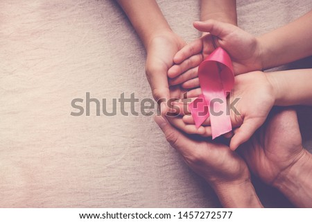 Family hands holding pink ribbon, breast cancer awareness, October pink concept, world cancer day #1457272577