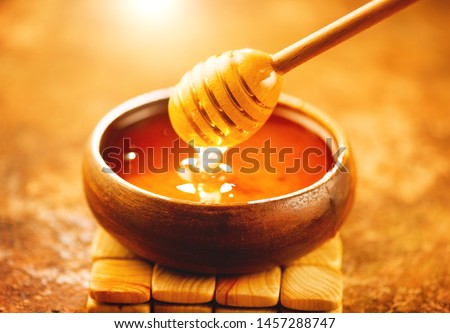 Honey dripping from honey dipper in wooden bowl.  Close-up. Healthy organic Thick honey dipping from the wooden honey spoon, closeup #1457288747