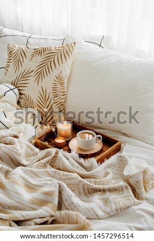 Wooden tray of coffee and candles on bed. White bedding sheets with striped blanket and pillow. Breakfast in bed. Hygge concept. #1457296514
