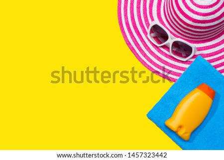 Beach accessories on the yellow background - sunglasses, towel, suntan cream and striped hat. summer is coming concept #1457323442