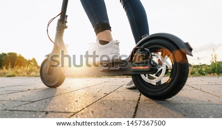 Young woman is ready to discover the urban city at sunset with electric scooter or e-scooter, Electric urban transportation concept image #1457367500
