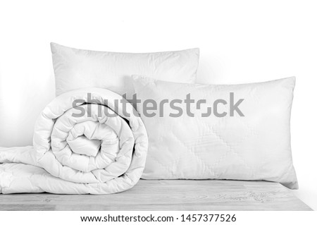 Two pillows and rolled duvet isolated on white. Bedding objects isolated against white background. Bedding items catalog  #1457377526