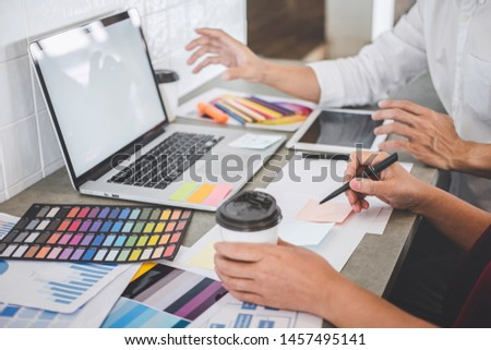 Teamwork of creative designers working on new project and choose color swatch samples for selection coloring on digital graphic tablet with work tools and equipment at workplace. #1457495141