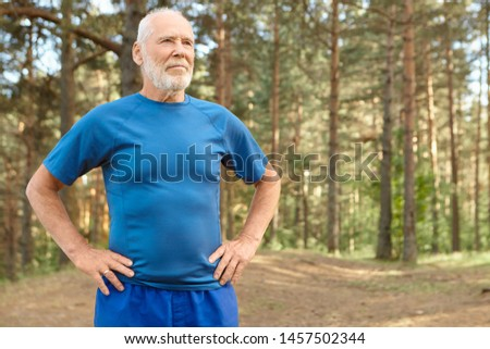 Self determined elderly man on retirement training outdoors in pine wood, holding hands on his waist, doing exercises to warm up body before run. Bearded retired male catching breath after workout #1457502344