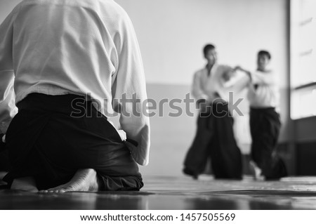 Aikido training. Black and white image. The teacher shows reception.  Traditional form of clothing in Aikido. Royalty-Free Stock Photo #1457505569