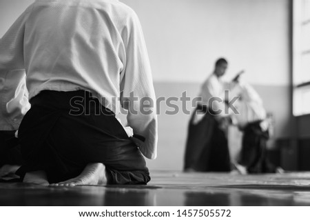 Aikido training. Black and white image. The teacher shows reception.  Traditional form of clothing in Aikido. Royalty-Free Stock Photo #1457505572