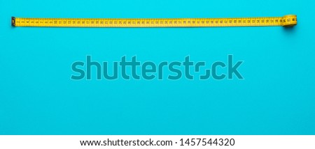 Top view of yellow soft measuring tape. Minimalist flat lay image of tape measure with metric scale over turquoise blue background with copy space. #1457544320