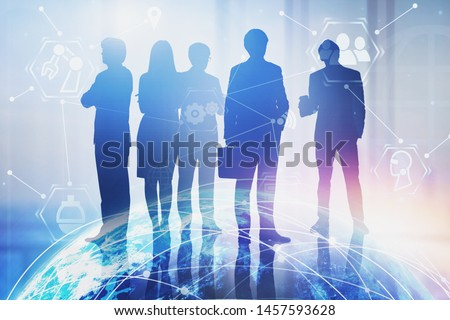 Silhouettes of business people working together in blurred office with double exposure of planet hologram and internet icons. Concept of hi tech. Toned image. Elements of this image furnished by NASA #1457593628