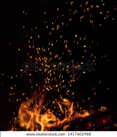 Burning sparks flying. Beautiful flames. Fiery orange glowing flying away particles on black background. #1457602988