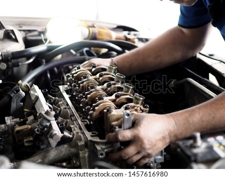 Car mechanic in garage with car engine after remove the cover part. #1457616980