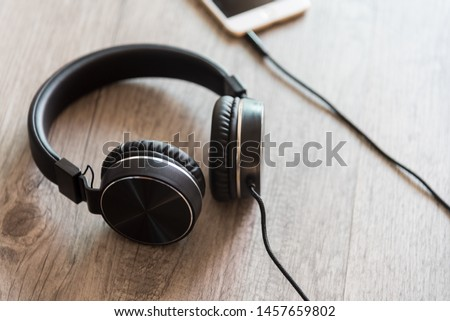 Black headphones and smartphone on wooden background. #1457659802
