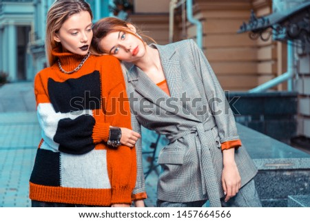 Leaning on shoulder. Red-haired model wearing grey suit leaning on shoulder of colleague while posing together #1457664566