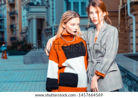 For fashion catalogue. Red-haired and blonde models posing outside for fashion catalogue in stylish outfits #1457664569