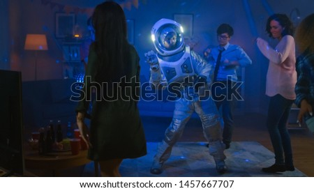 At the College House Costume Party: Fun Guy Wearing Space Suit Dances Off, Doing Robot Dance Modern Moves. With Him Beautiful Girls and Boys Dancing in Neon Lights. #1457667707