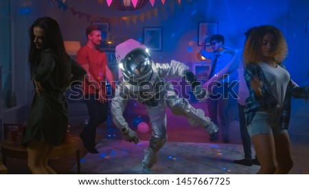 At the College House Costume Party: Fun Guy Wearing Space Suit Dances Off, Doing Robot Dance Modern Moves. With Him Beautiful Girls and Boys Dancing in Neon Lights. #1457667725